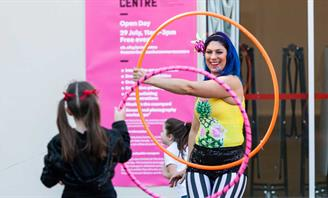 Photo of performer holding hoola hoop class