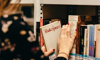 Photo of a person taking a book from a shelf