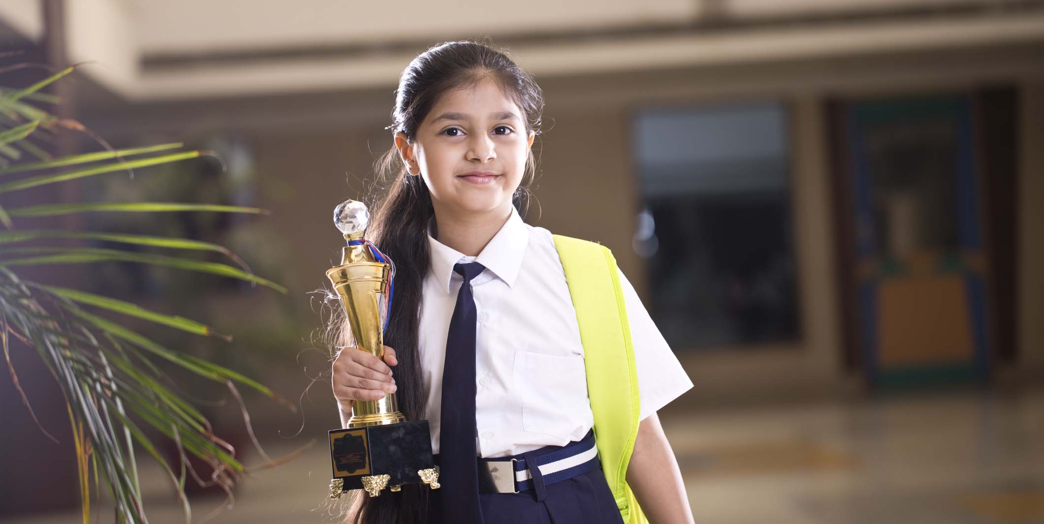 Young Girl in a school uniform holding an award