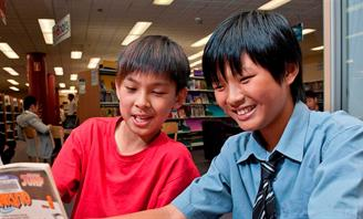 Photo of two teen boys reading a book