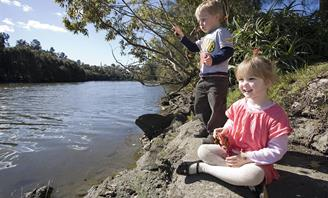 Photo of children sitting on the shores of the Cooks River