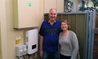 Photo of couple standing in front of solar power inverter mounted on external wall