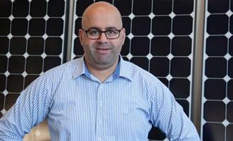 Photo of a Mayor Khal Asfour in front of Solar Panels