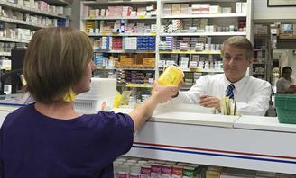 Photo of resident disposing of Sharps container at pharmacy