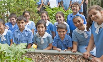 Photo of children in front of vege garden